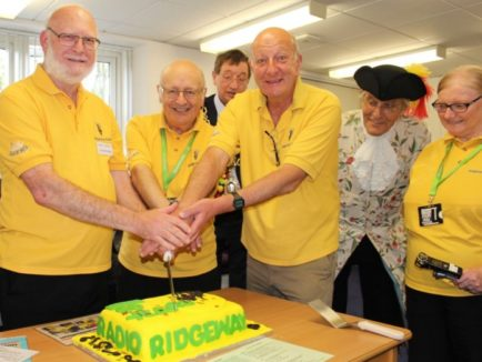 Photo of CUTTING the cake are Andy Worth, Peter Foster and Andy Venton watched by Mayor Tim Harries, Town Crier Alistair Chisholm and fellow broadcaster Heather Foster